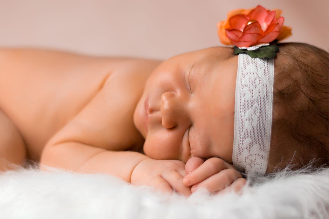 Novorđena beba sa trakom za kosu i crvenom ružom