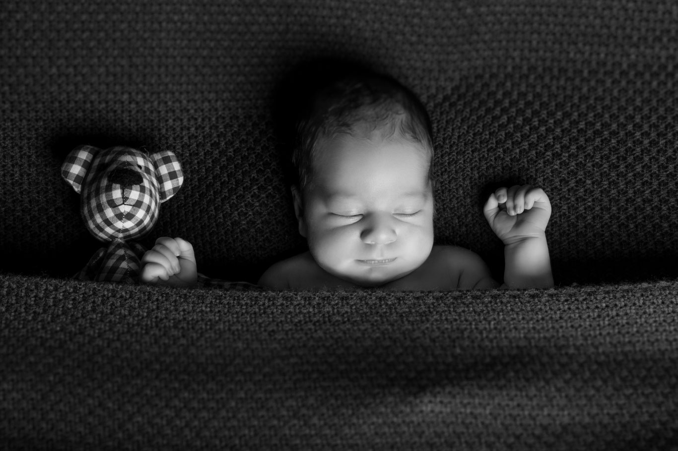 monohromatska slika novorođene bebe kako leži pokrivena do ramena sa plišanim medom.