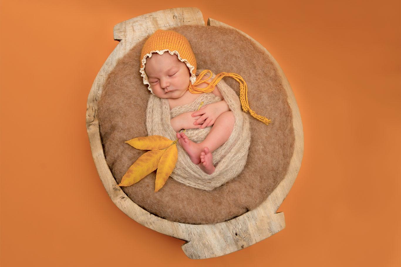 prelepa novorođena devojčica u drvenom lavoru na narandžastoj podlozi