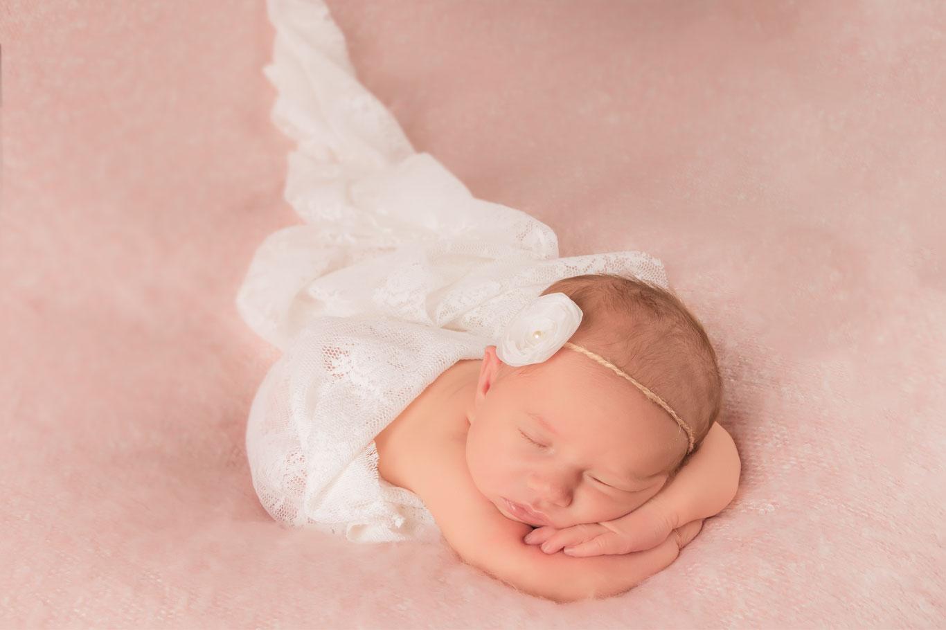 novorođena devojčica leži na stomaku sa rukicama ispod glave na roze pokrivaču