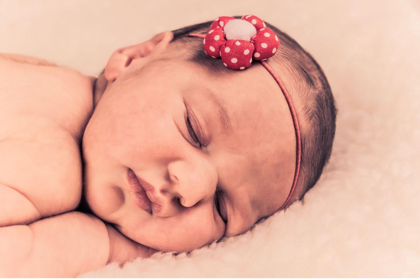 bebica sa crvenim cvetom u kosi