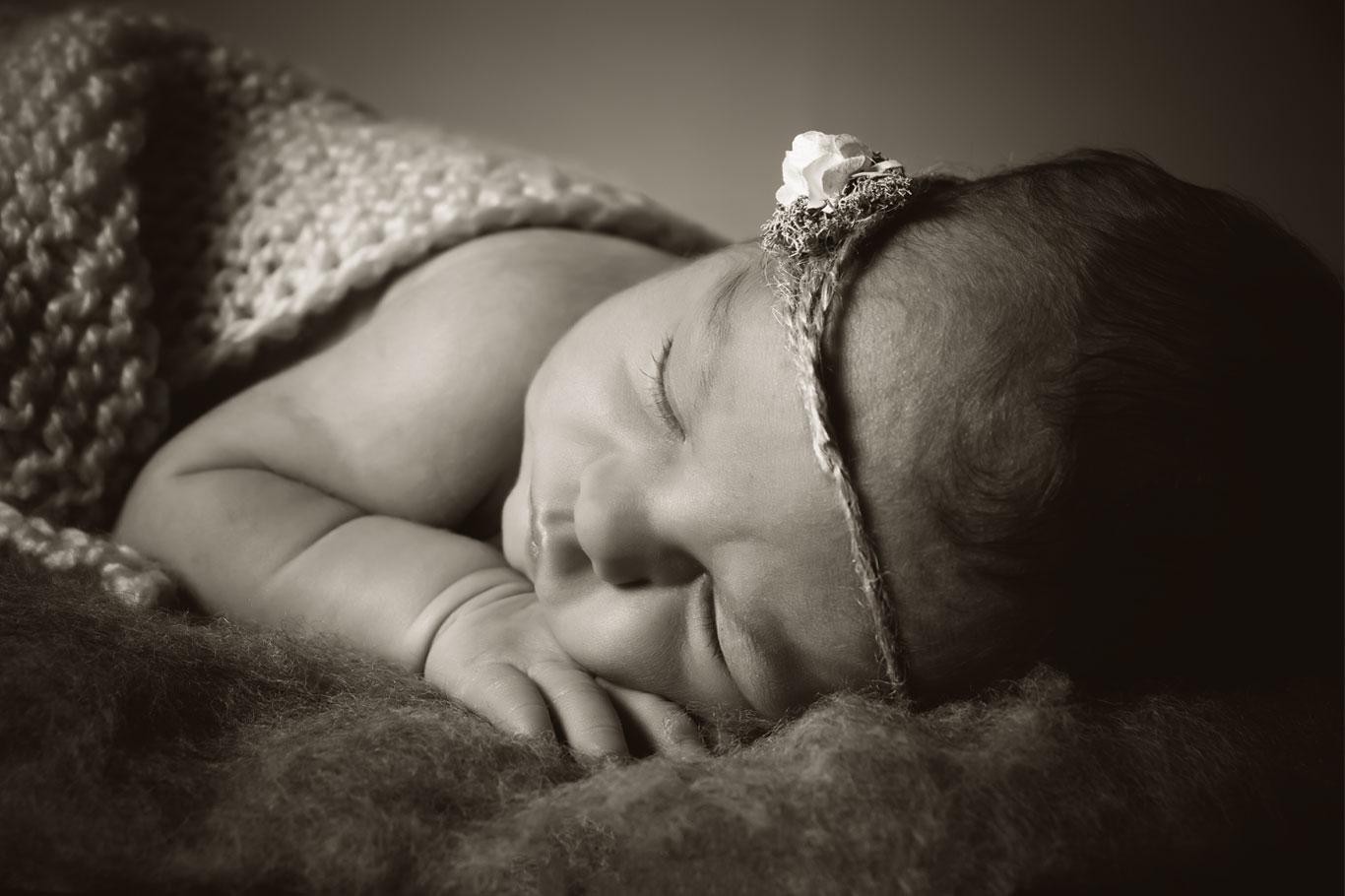 beba sa cvetom u kosi spava u polumraku
