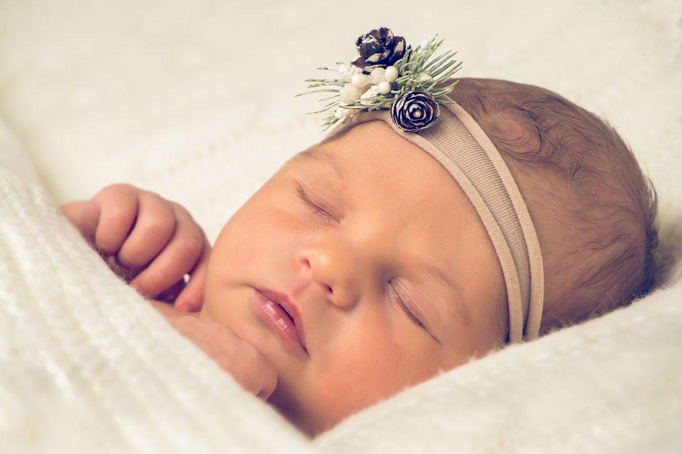 novorođena beba spava sa grančicom jele i šišarkom u kosi
