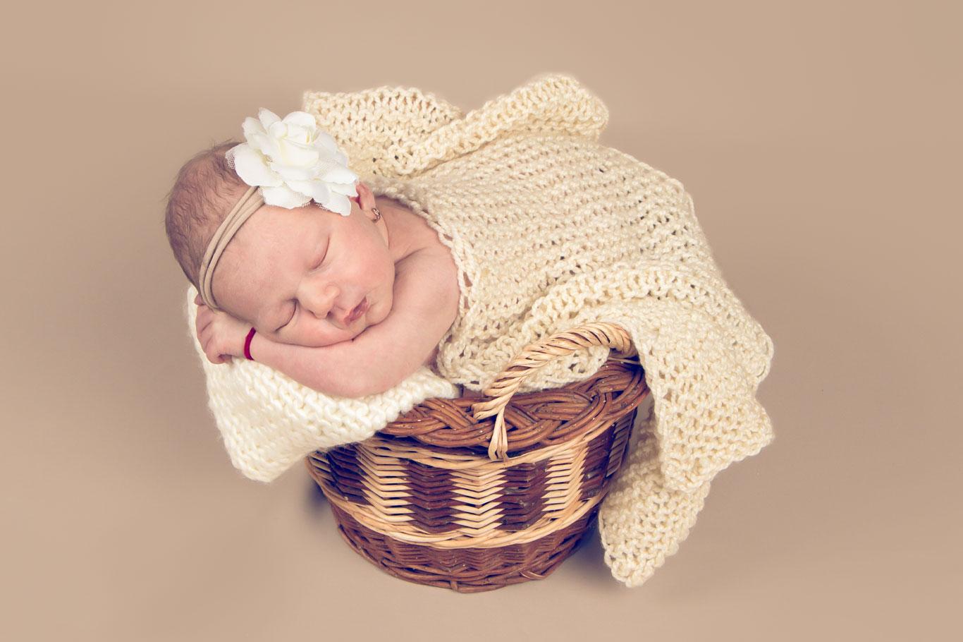 novorođena beba sa belim cvetom u kosi spava u pletenoj korpici