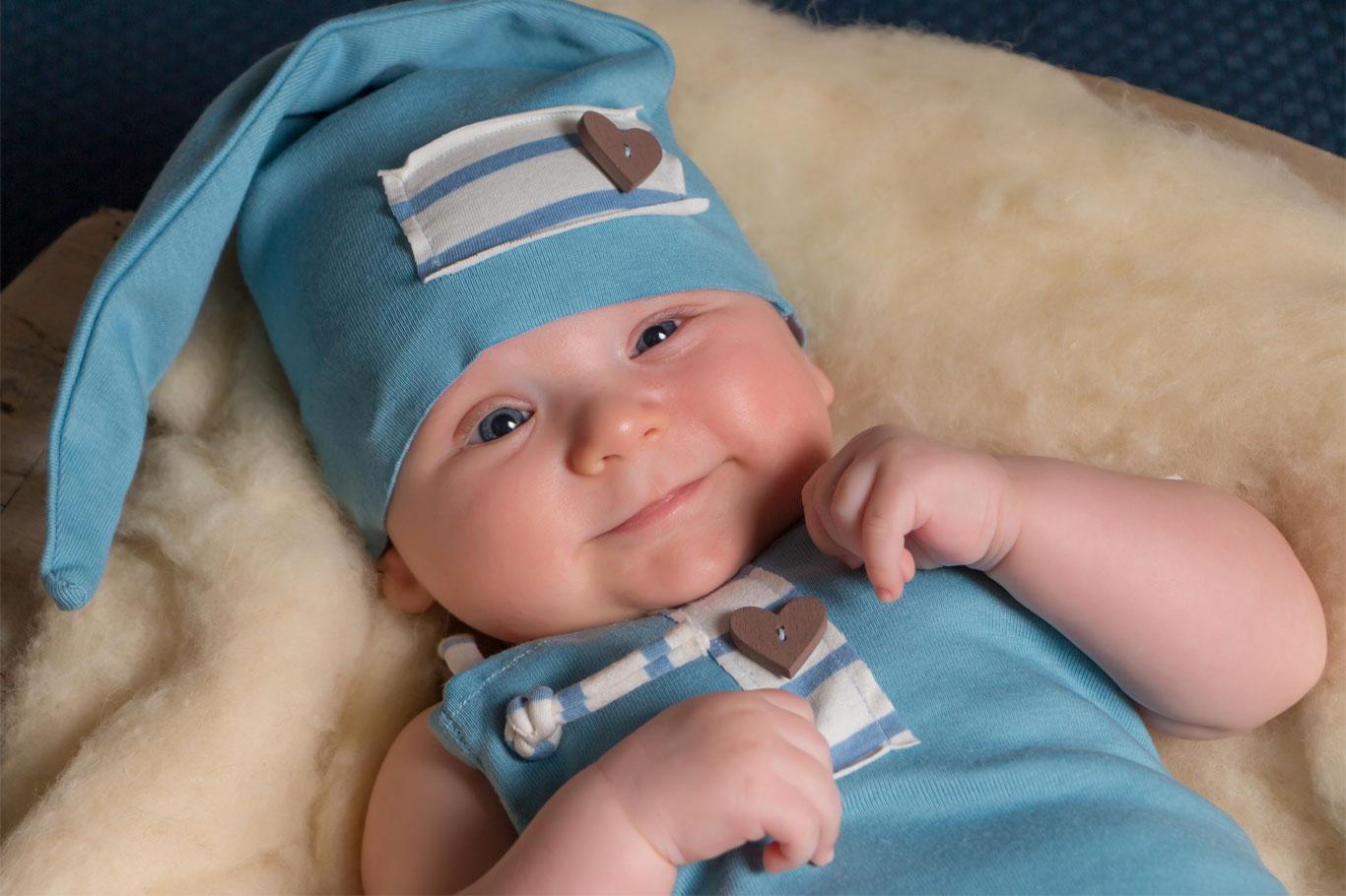 nasmejani novorođeni dečak u plavom kombinezonu sa plavom kapom