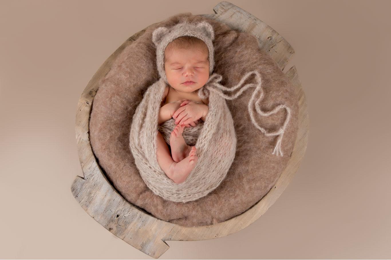 novorođena beba spava u drvenom lavoru na drap pozadini