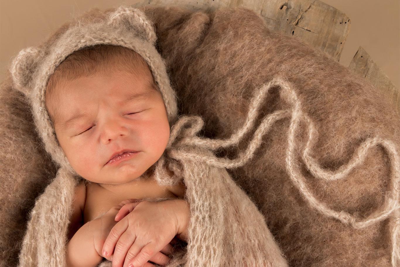novorođena beba sa kapicom spava na braon prekrivaču