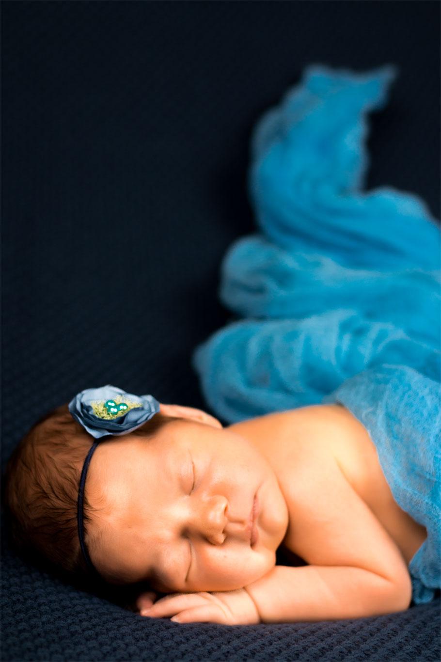 novorođena beba sa plavim cvetom u kosi i plavim prekrivačem