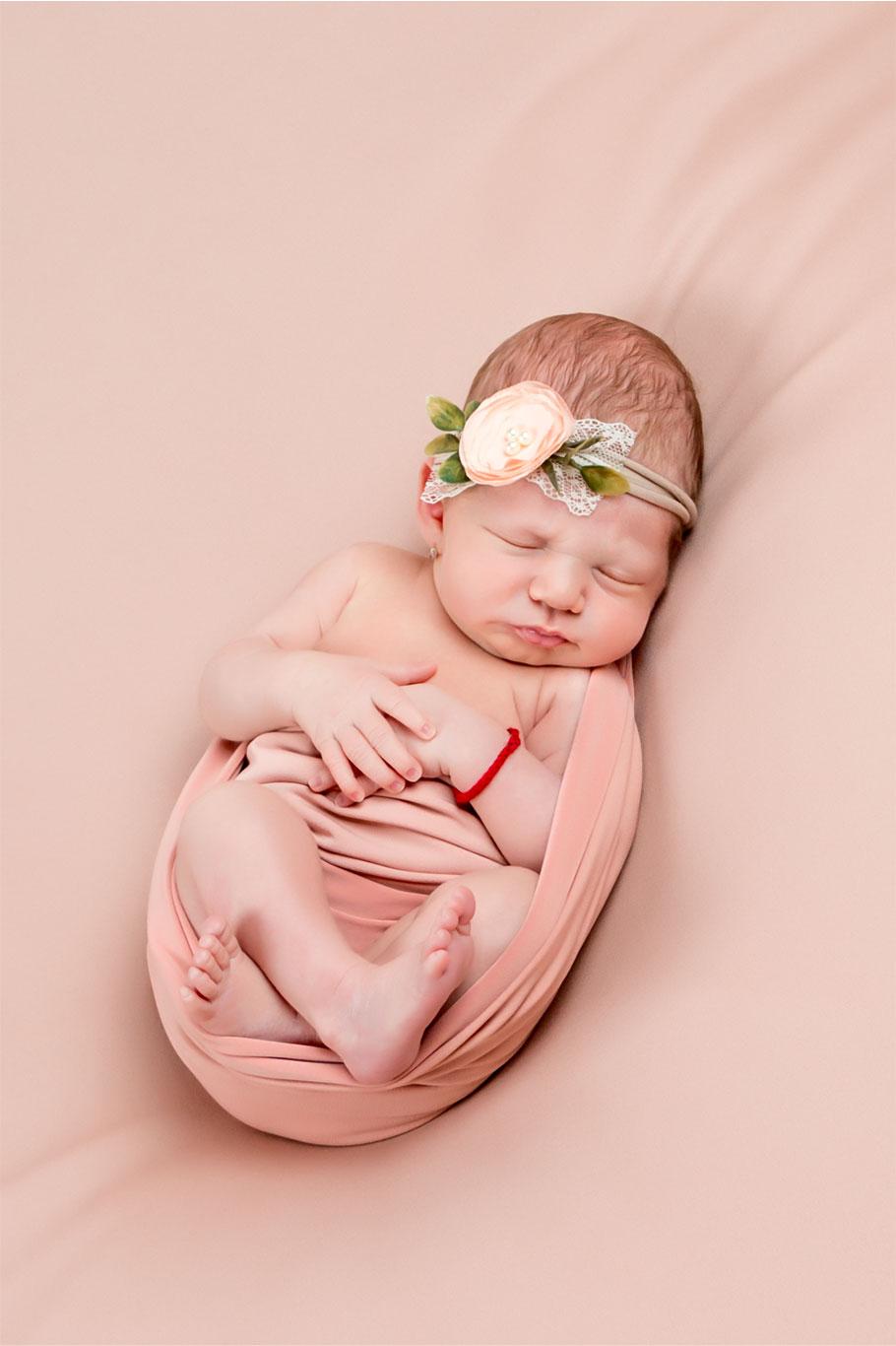 nežna slika bebe sa roza cvetom u kosi na roza prekrivaču