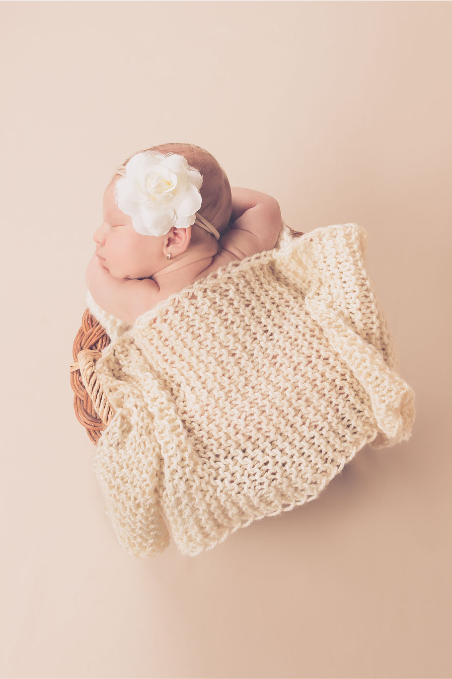 beba spava na stomaku sa belim cvetom u kosi